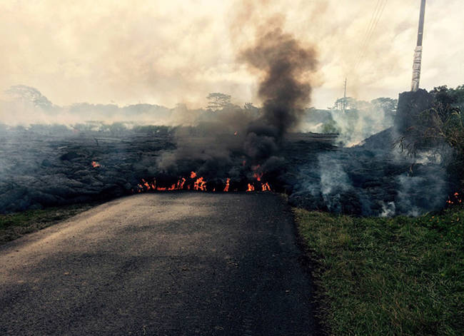 The flow of lava in this photo is moving from right to left across a road.