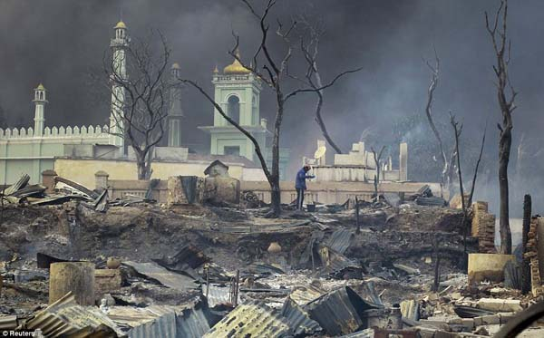 A man stands in front of his burned mosque in Meikhtila, Myanmar.