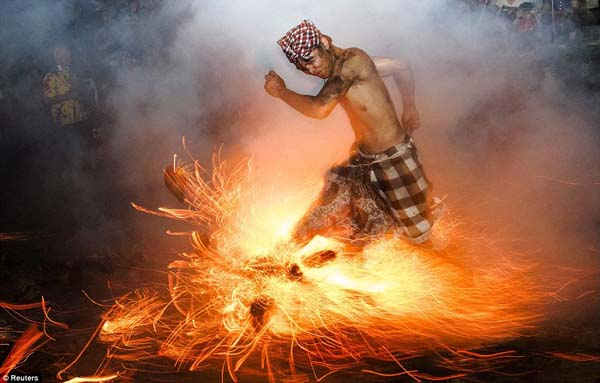 This Balinese man kicks up fire during the Perang Api (Fire War) ritual ahead of Nyepi day.