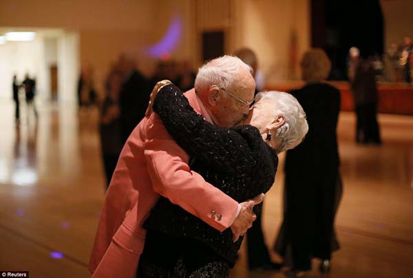 A man kisses his sweetheart at the end of a dance during a gala at a retirement community.