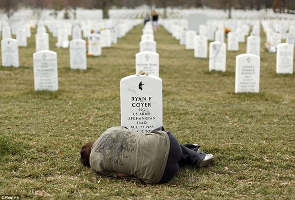 A woman mourns in front of the grave of her brother in Arlington National Cemetery.