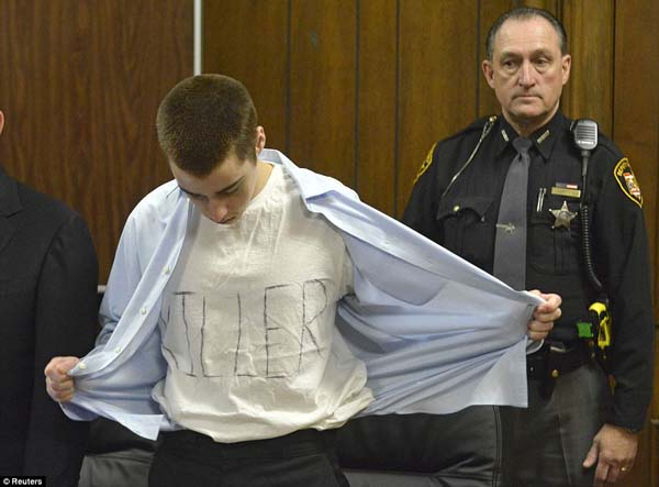 "TJ Lane takes off his shirt to reveal a t-shirt that says ""killer"" after he was sentenced to prison for life without parole after killing three students during a shooting rampage."