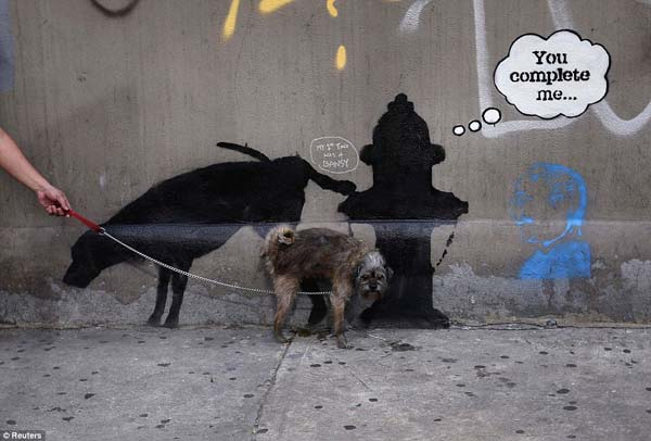 A dog urinates on a new work by British graffiti artist Banksy.