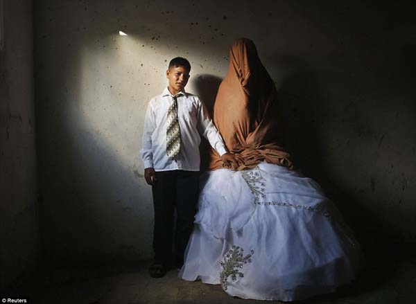 A child bride and groom stand together before their wedding.