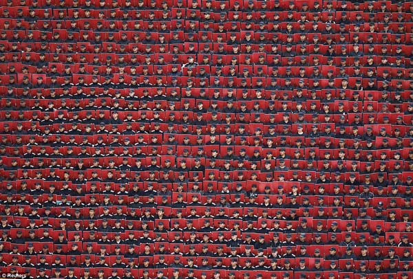 Troops hold colored cards during a military parade in Mexico City.
