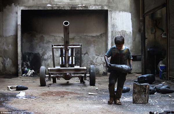 A 10 year-old boy carries a mortar shell in a weapons factory for the Free Syrian Army.