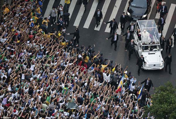 Pope Francis greets a crowd from his Popemobile.